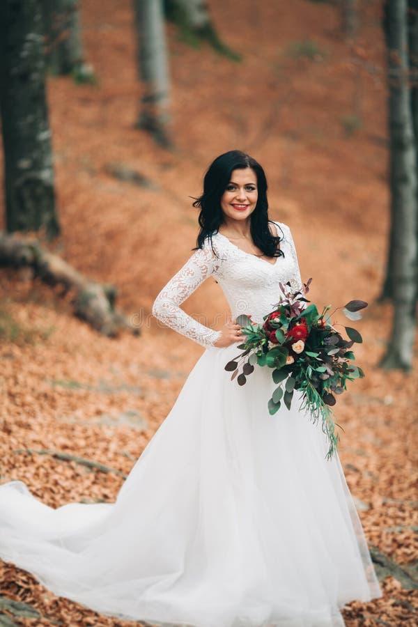 Schitterende donkerbruine bruid in het elegante het boeket van de kledingsholding stellen dichtbij bos en meer stock fotografie