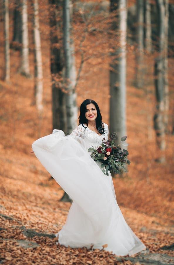 Schitterende donkerbruine bruid in het elegante het boeket van de kledingsholding stellen dichtbij bos en meer royalty-vrije stock foto's