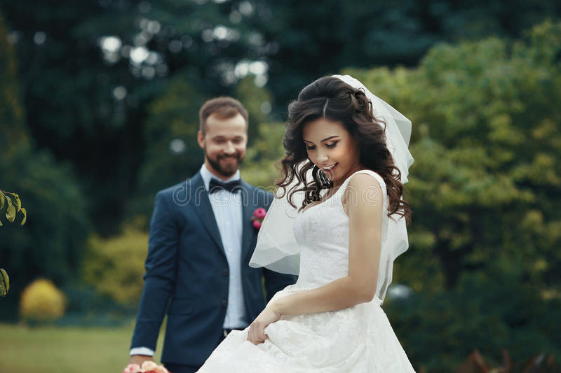 Schitterende donkerbruine bruid in het elegante kleding stellen in het park met stock afbeelding