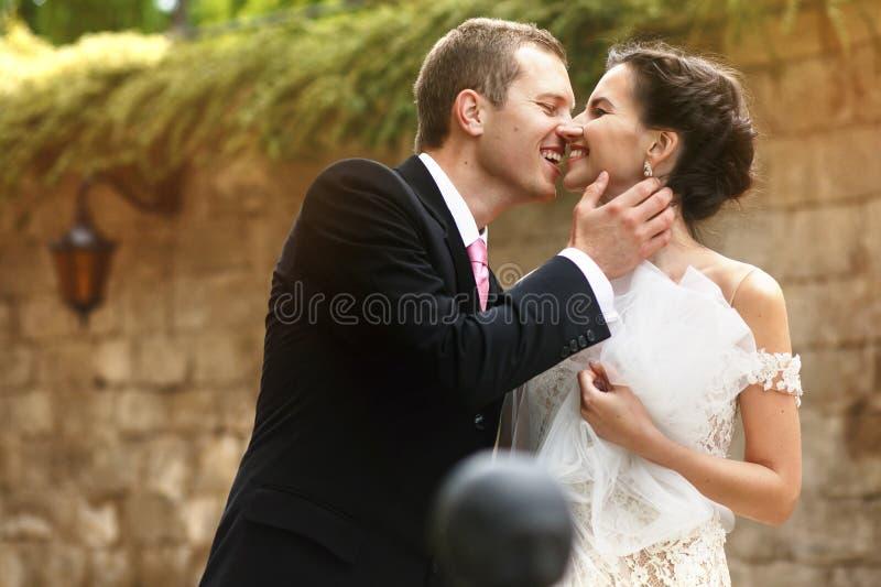 Schitterende donkerbruine seksuele bruid die met knappe bruidegom in c lachen stock foto
