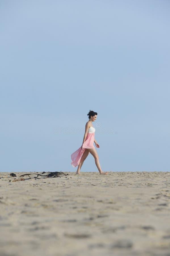 Schitterende donkerbruine vrouw die in kleding in het woestijnzand lopen stock foto's