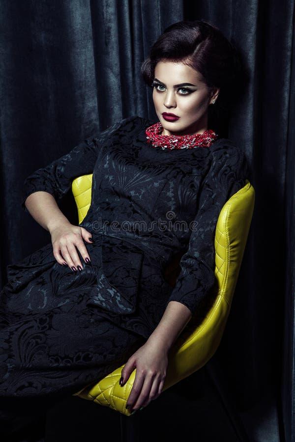 Schitterende donkerbruine vrouw met modieuze make-up en kapsel die zwarte avondjurk dragen die terwijl het zitten op gele stoel s stock foto