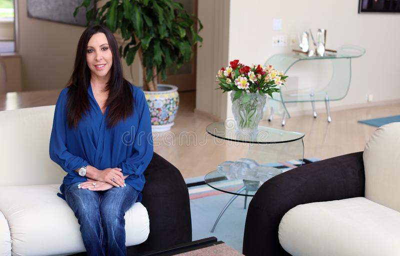 Schitterende donkere haarvrouw die met mooi blauw overhemd, professionele psycholoog in een art decoruimte glimlachen stock fotografie
