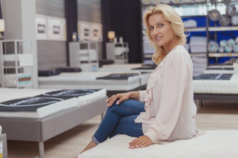 Schitterende elegante rijpe vrouw die voor nieuw orthopedisch bed winkelen royalty-vrije stock afbeeldingen