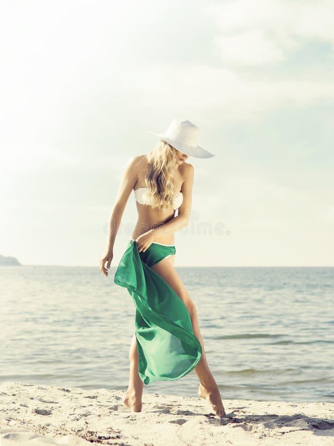 Schitterende, elegante vrouw met hete benen die op het strand in gre stellen royalty-vrije stock foto's