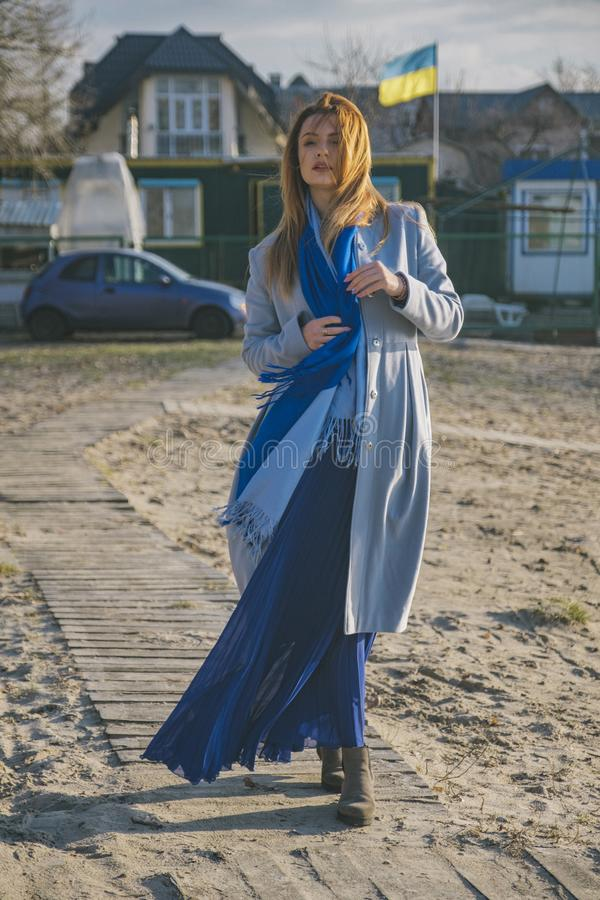 Schitterende Europese vrouw in warme laag en kleding op een gang in park dichtbij rivier Winderig weer Haar klerenvlieg in de win royalty-vrije stock afbeeldingen