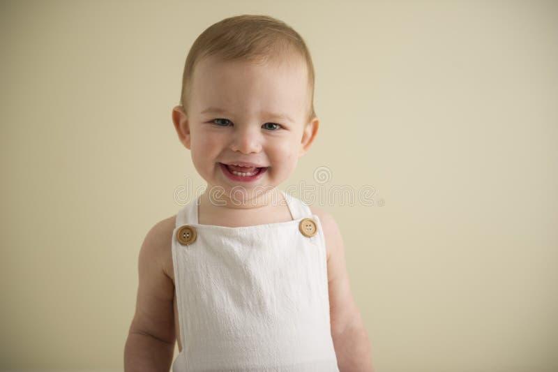 Schitterende gelukkige blauwe eyed babyjongen in neutrale tonen stock afbeeldingen