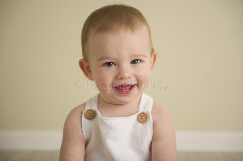 Schitterende gelukkige blauwe eyed babyjongen in neutrale tonen royalty-vrije stock fotografie