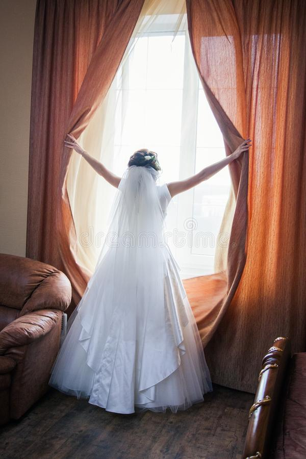 Schitterende gelukkige luxe modieuze donkerbruine bruid dichtbij een venster stock foto's