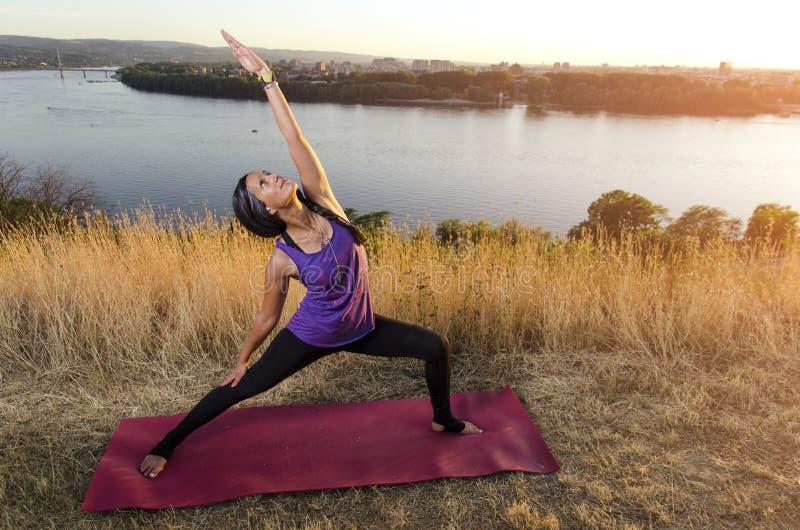 Schitterende geschikte vrouw die yogaoefeningen doen stock fotografie
