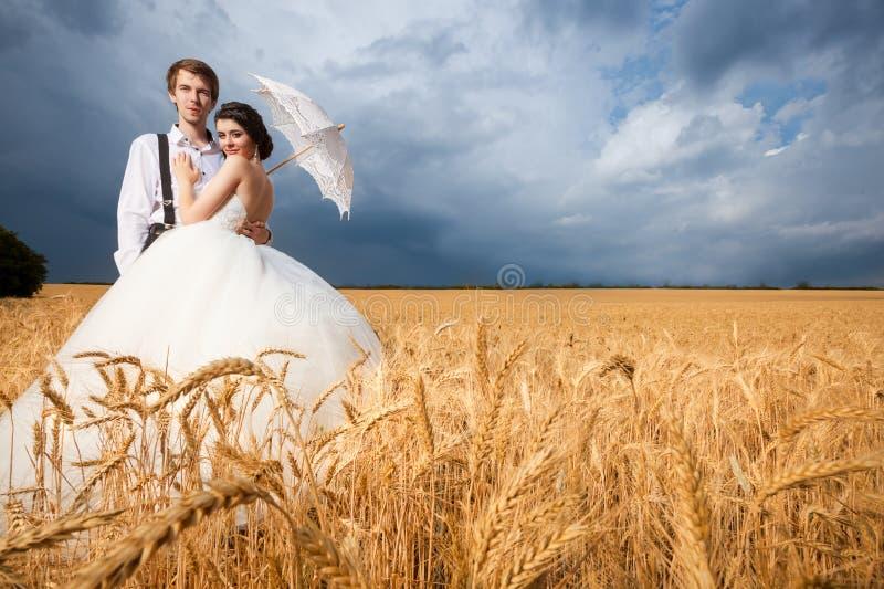 Schitterende jonge bruid en bruidegom op tarwegebied met dramatische hemel royalty-vrije stock fotografie