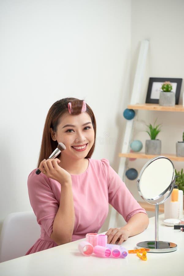 Schitterende jonge donkerbruine vrouw die make-up toepassen royalty-vrije stock afbeelding