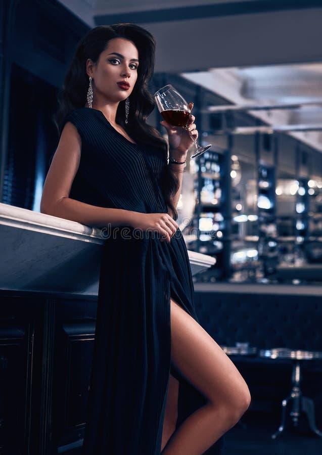 Schitterende jonge donkerbruine vrouw in donkere kleding met wijn stock fotografie
