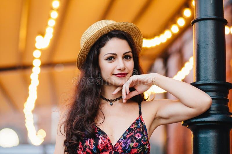 Schitterende jonge elegante vrouw met het aantrekkelijke verschijning stellen bij terras, gekleed in strohoed en de zomerkleding, royalty-vrije stock fotografie