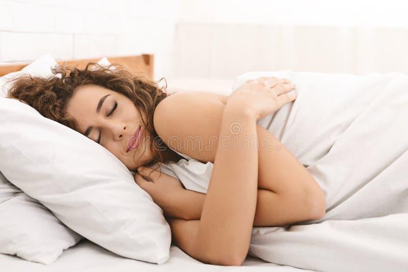 Schitterende jonge vrouw die koesteren terwijl het slapen stock foto's