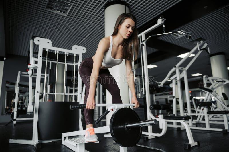Schitterende jonge vrouw die met handgewichten uitwerken om haar slank cijfer goed gevormd te houden stock foto's