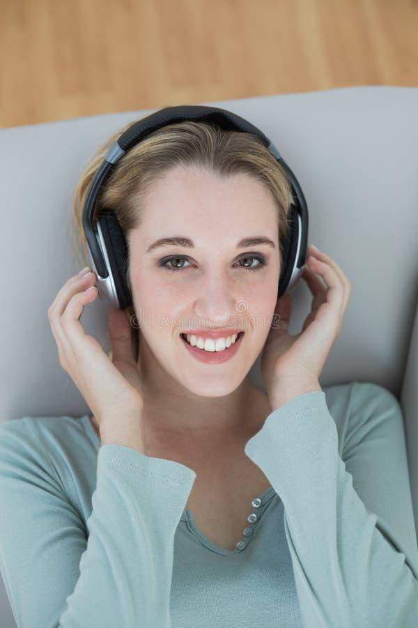 Schitterende jonge vrouw die met hoofdtelefoons aan muziek luisteren die bij camera glimlachen stock afbeelding