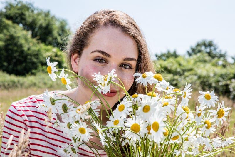 Schitterende jonge vrouw die met kamillebloemen glimlachen voor natuurlijke schoonheid stock foto's
