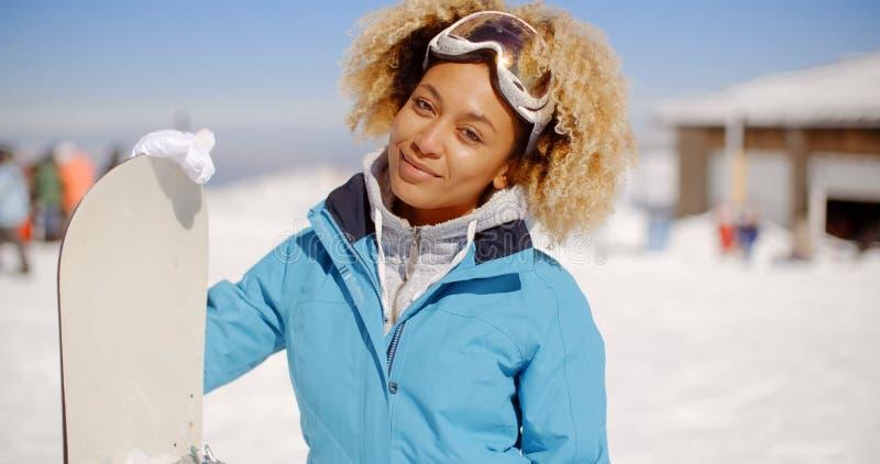 Schitterende in jonge vrouw met haar snowboard stock afbeelding