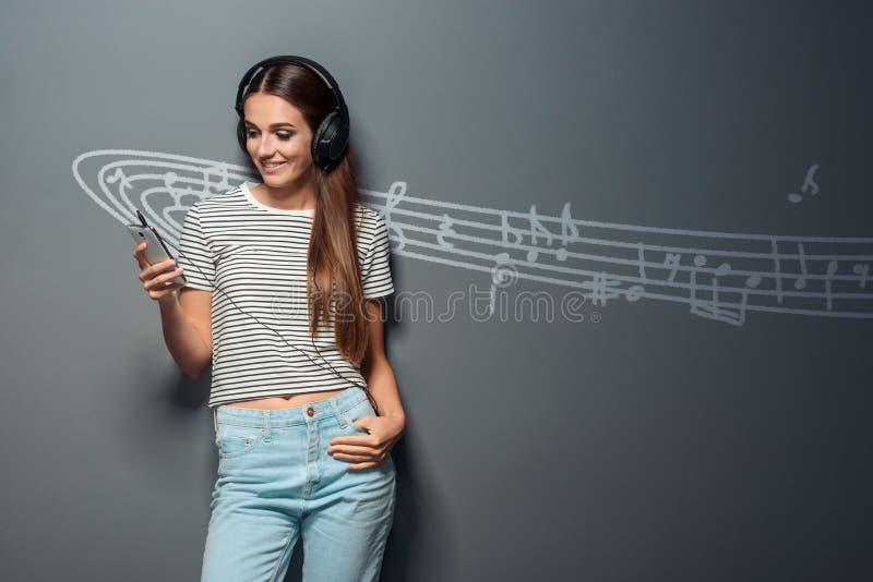 Schitterende jonge vrouw met hoofdtelefoons royalty-vrije stock afbeeldingen