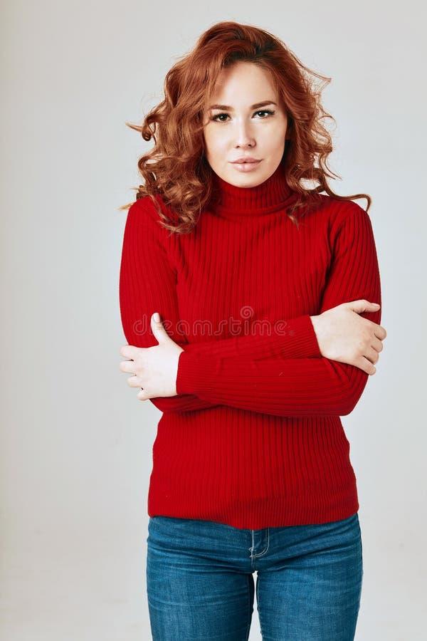 Schitterende jonge vrouw met lang rood krullend haar in rode sweater op witte achtergrond royalty-vrije stock foto's