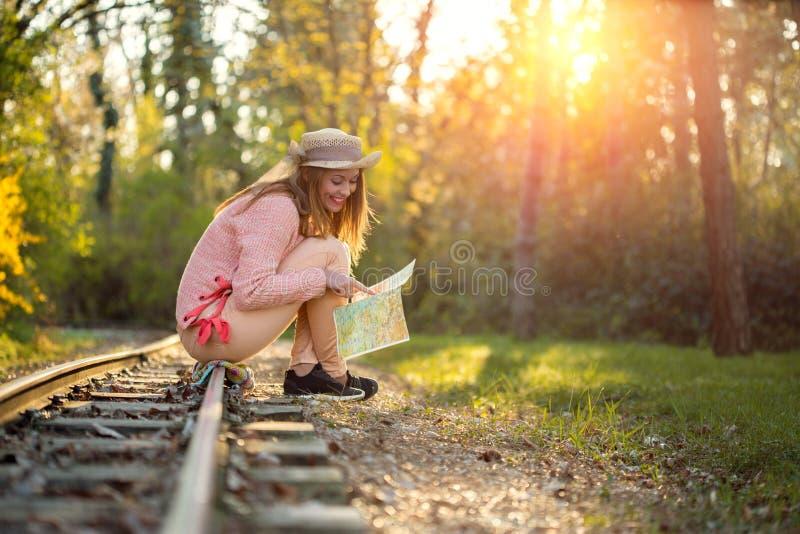 Schitterende jonge vrouwenzitting op een spoorweg die een kaart bekijken stock fotografie