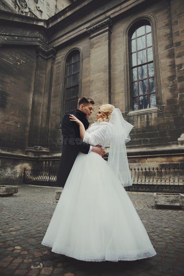 Schitterende jonggehuwdebruid in witte laag en knappe valenty bruidegom stock afbeelding