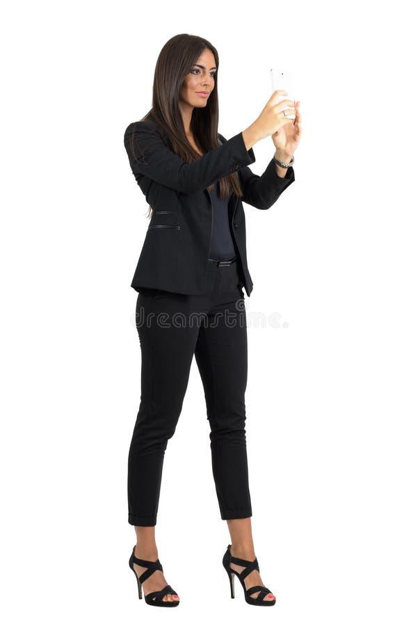 Schitterende mannequin in zwart kostuum die foto met smartphone nemen royalty-vrije stock afbeeldingen