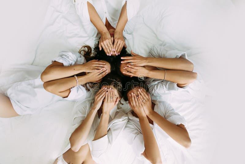 Schitterende meisjes in de witte overhemden op het bed royalty-vrije stock foto
