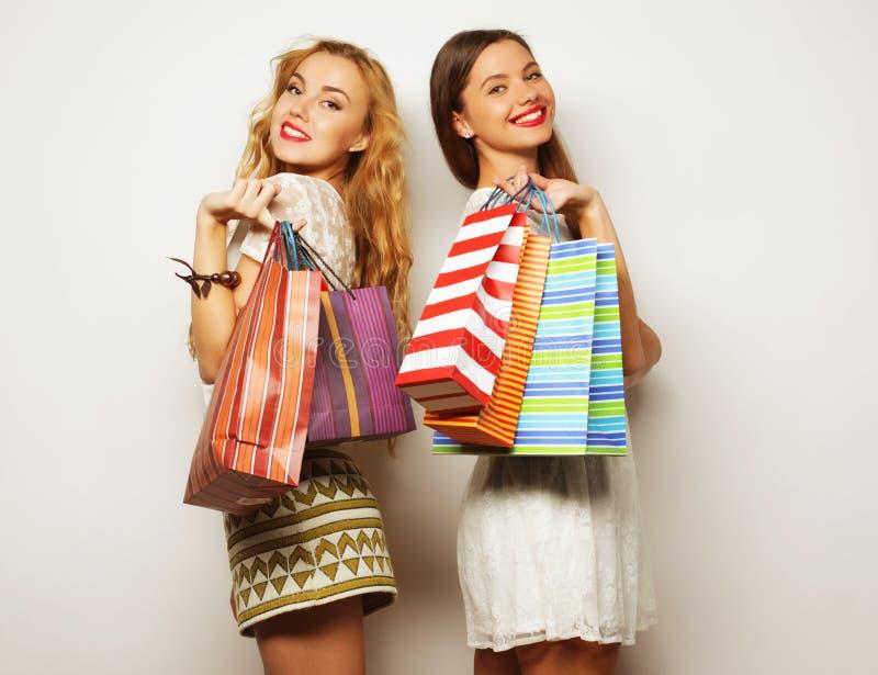 Schitterende meisjes die met papieren zakken camera bekijken royalty-vrije stock foto