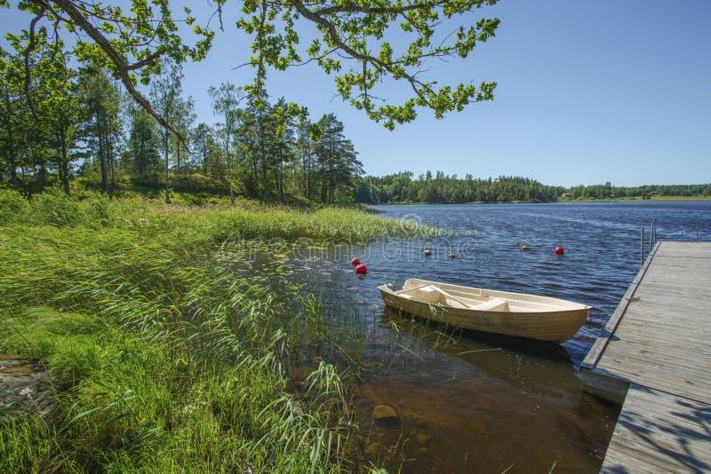 Schitterende mening van eenzame lege houten die boot bij de houten pijler wordt geparkeerd De schitterende achtergronden van het  stock fotografie