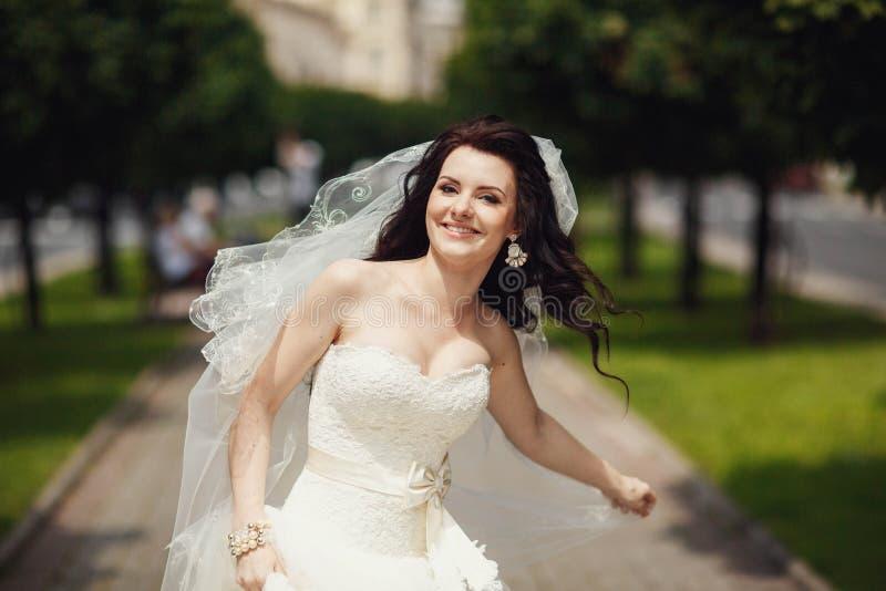 Schitterende modieuze donkerbruine bruid die in uitstekende witte kleding binnen loopt royalty-vrije stock foto's