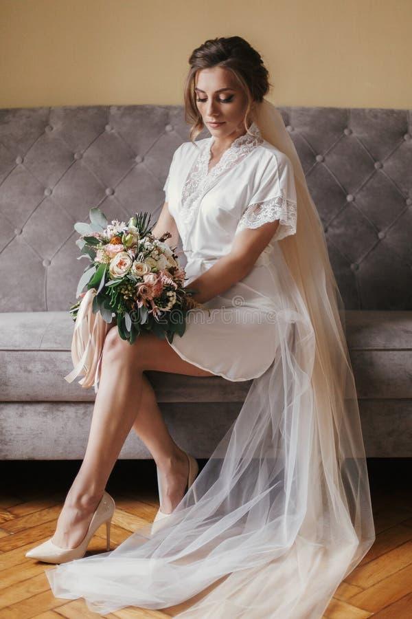 Schitterende mooie bruid die in zijderobe modern boeket houden en royalty-vrije stock afbeeldingen