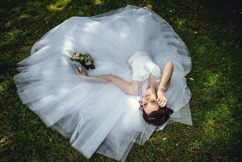 Schitterende mooie bruid in een witte kleding die op het groene gras in het Park met een boeket van bloemen in haar handen liggen stock foto