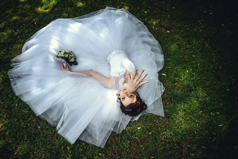 Schitterende mooie bruid in een witte kleding die op het groene gras in het Park met een boeket van bloemen in haar handen liggen stock fotografie