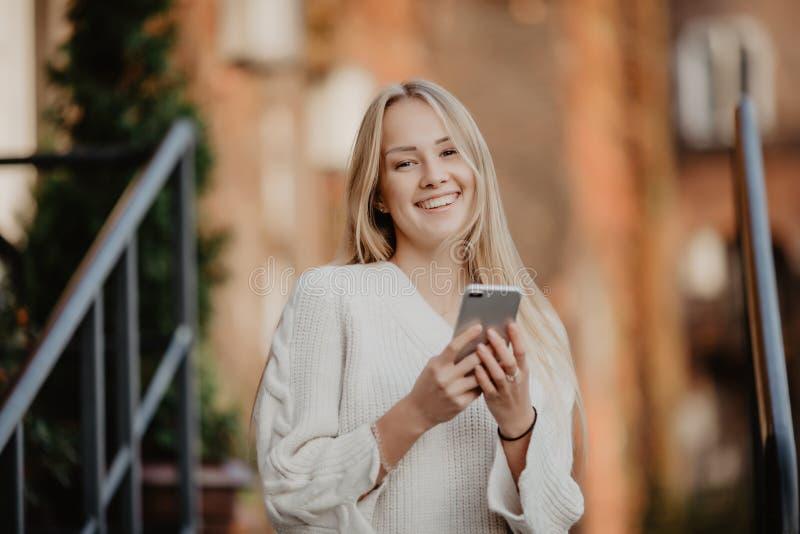 Schitterende mooie jonge vrouw met het overseinen van het blondehaar op Smartphone bij de achtergrond van de stadsstraat royalty-vrije stock afbeeldingen