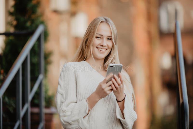 Schitterende mooie jonge vrouw met het overseinen van het blondehaar op Smartphone bij de achtergrond van de stadsstraat stock afbeelding