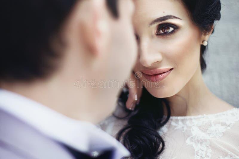 Schitterende onschuldige donkerbruine bruid die knap bruidegomgezicht bekijken royalty-vrije stock fotografie