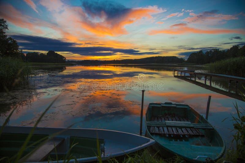 Schitterende oranje die zonsondergang in het kalme water wordt weerspiegeld royalty-vrije stock foto