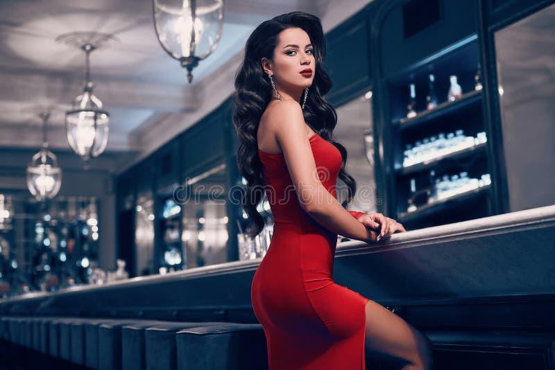 Schitterende schoonheids jonge donkerbruine vrouw in rode kleding stock foto