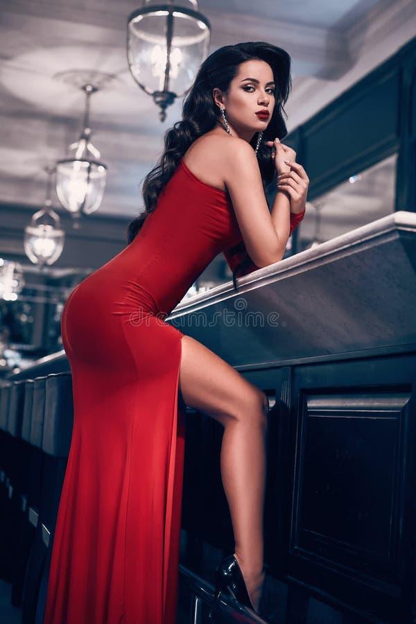 Schitterende schoonheids jonge donkerbruine vrouw in rode kleding stock foto's