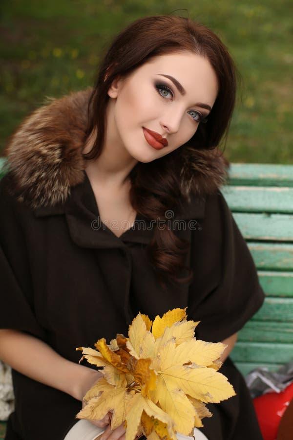 Schitterende sensuele vrouw met donker haar in elegante kleren en luxueuze laag, royalty-vrije stock afbeeldingen