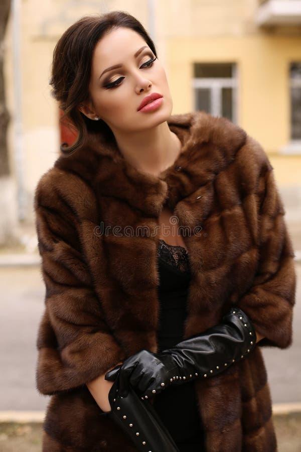 Schitterende sensuele vrouw met donker haar in luxueuze bontjas en leerhandschoenen stock foto's