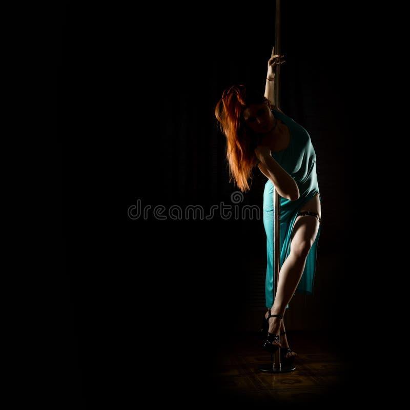 Schitterende sexy danser in nachtclub vrouw in een lange turkooise kleding met een spleet op een donkere achtergrond Vrije ruimte royalty-vrije stock afbeelding