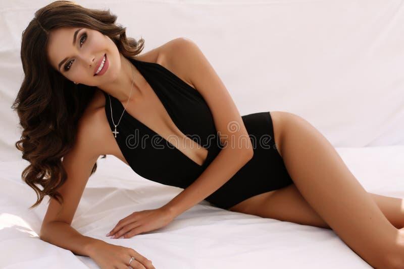 Schitterende sexy vrouw met donker haar in elegant zwempak stock foto