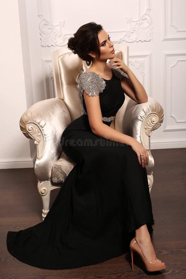 Schitterende sexy vrouw met donker haar in luxueuze kleding stock afbeelding
