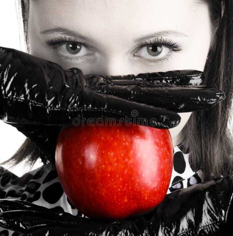 Schitterende vrouw die een rode appel houdt royalty-vrije stock afbeeldingen