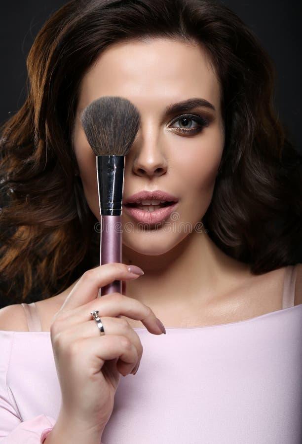 Schitterende vrouw die met donker haar haar make-up beëindigen gebruikend poeder stock foto's