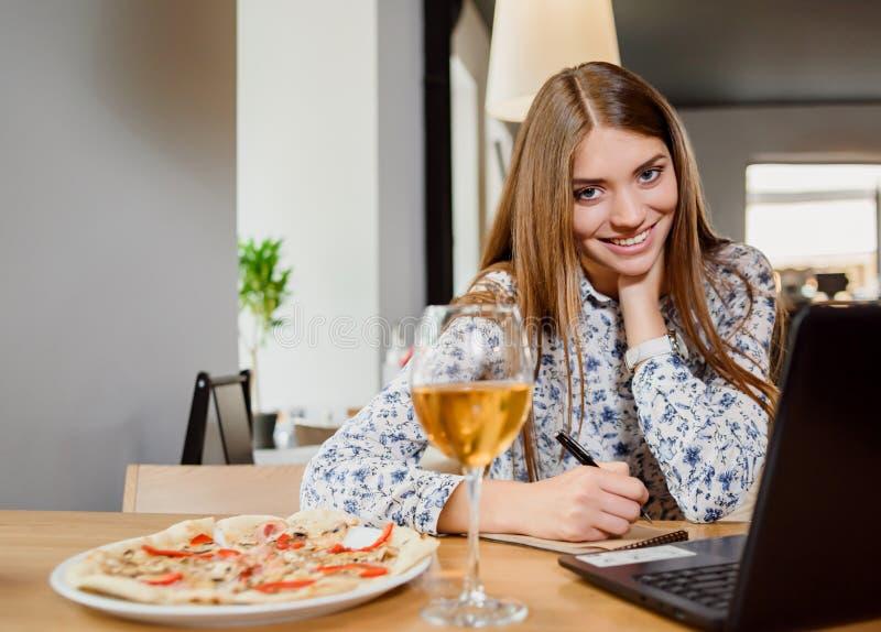 Schitterende vrouw die met notitieboekje in restaurant werken stock fotografie