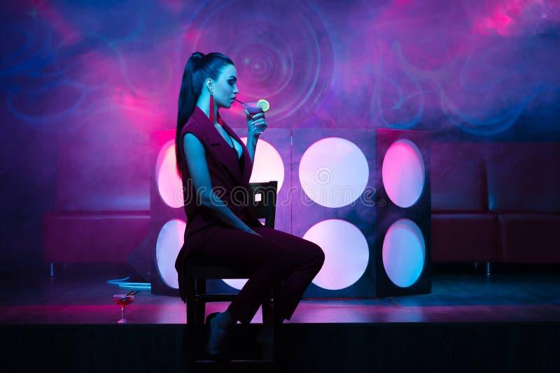 Schitterende vrouw die in nachtclub een cocktailzitting op stoel drinken royalty-vrije stock fotografie